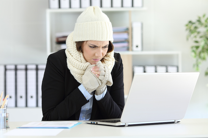 why am i always cold- woman in winter clothes at desk