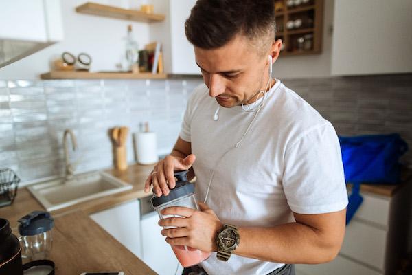 whey vs plant protein - man making shake