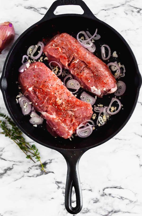 baked pork chops - raw pork chop in pan