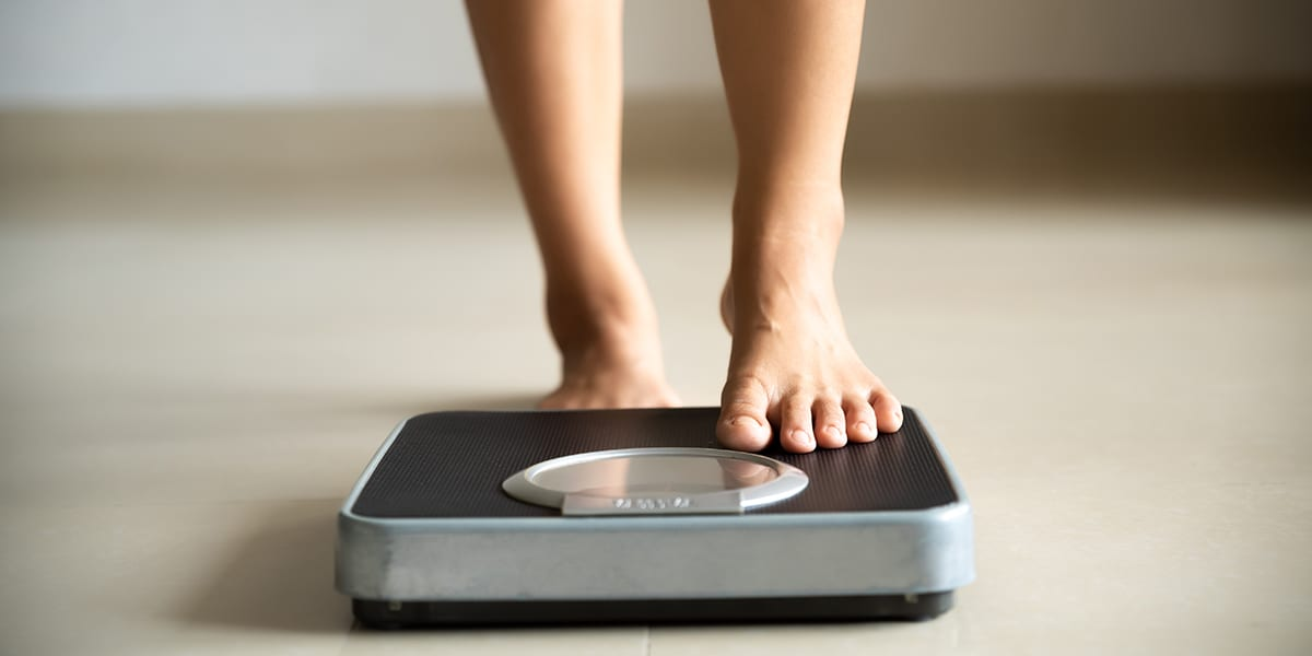 muscle loss - woman stepping on scale