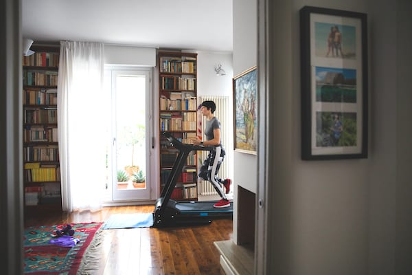 running in isolation - woman running on treadmill at home