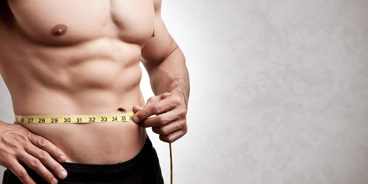 muscle mass loss - man measuring abs