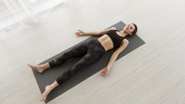breathwork - woman laying on yoga mat