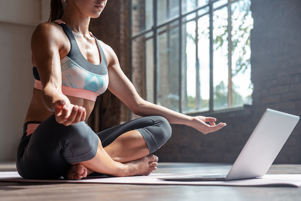 yoga studio at home - woman taking online yoga class