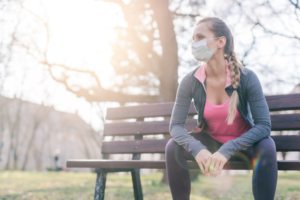 running during coronavirus - woman on bench with mask