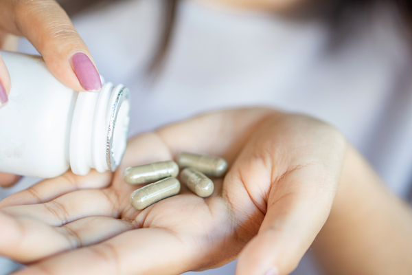 nad supplements - woman putting pills in hand