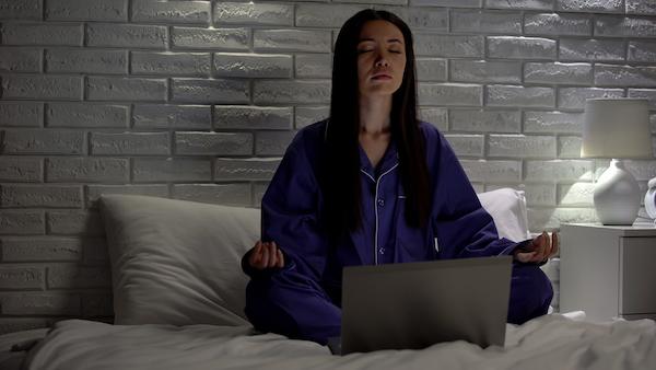 sleep meditation - woman meditating in bed