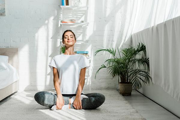 woman meditating on floor of bedroom | wellness routine