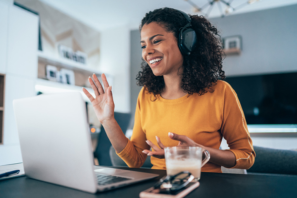 woman in headphones on computer at home | wellness routine
