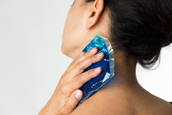 woman applying icepack to neck | headache remedies