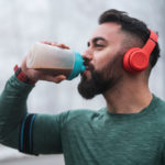 man drinking protein outside | how many grams of protein do you need after a workout