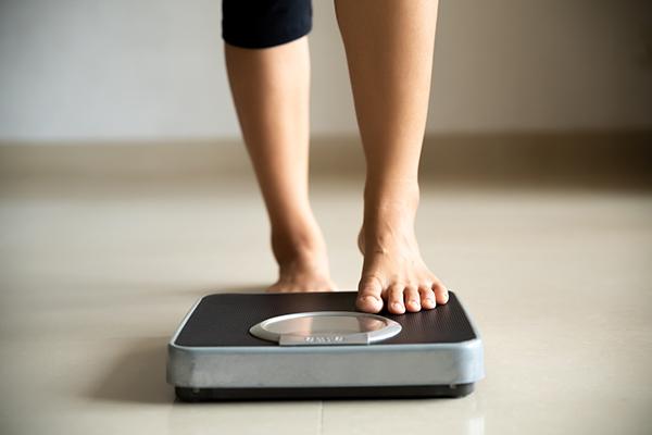 woman weighing herself | fitness goals