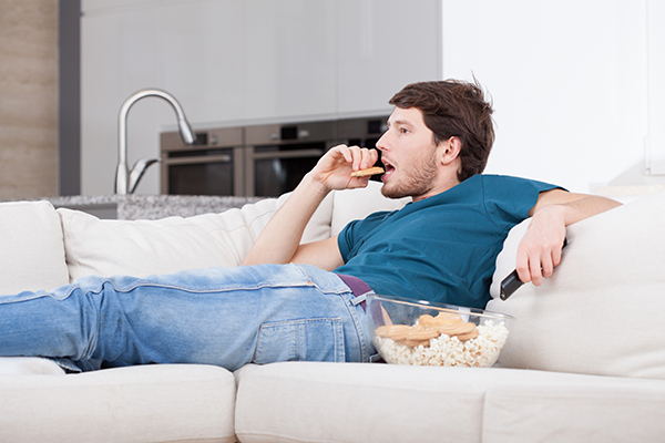 man watching tv while eating snacks | fitness goals