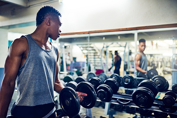 man looking in mirror while lifting weights | fitness goals