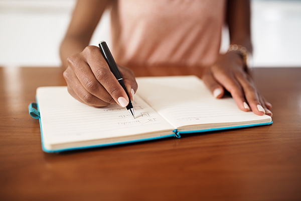 woman writing in planner | daily meditation tips