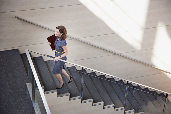 businesswoman walking up stairs | how many steps a day