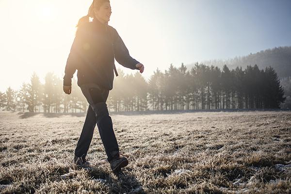 woman walking through field in winter | walking for fitness