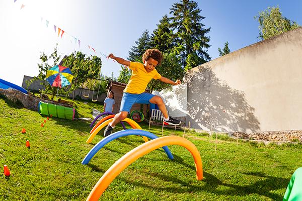 child doing hurdles in backyard   homeschool pe ideas