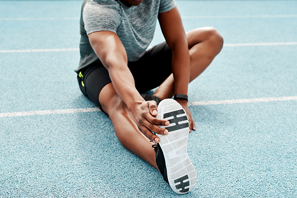 athlete static stretching on track | openfit trainers habits