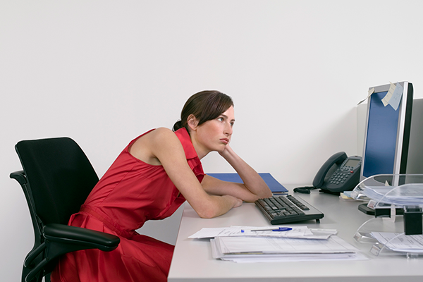 woman slouching at office desk | openfit trainers habits