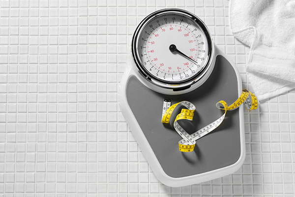 scale and tape measurer on the floor | pre-workout for weight loss
