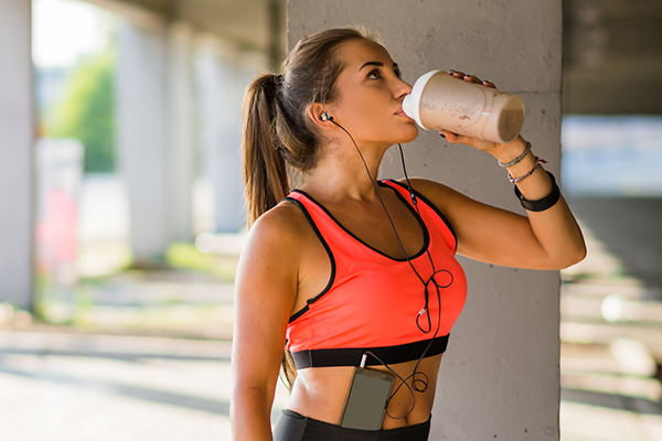 athletic woman drinking protein shake after workout | meal replacement plant based shakes