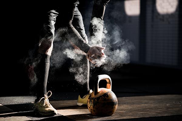 man using chalk to lift kettlebell | weight gain supplements