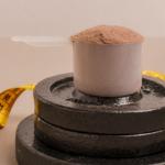 scoop of supplement on top of weights | weight gain supplements