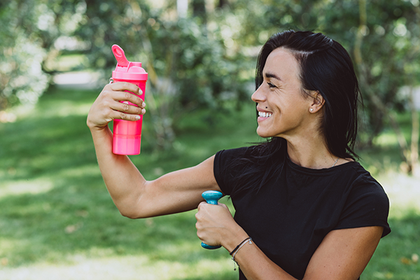 woman with dumbbell looking at protein shake | reasons to take protein