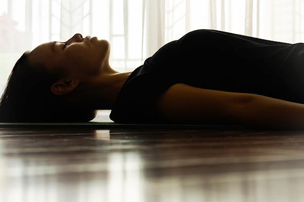 woman meditating lying down | how long should you meditate
