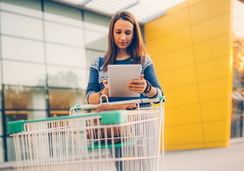 woman looking at tablet outside store | thanksgiving guide