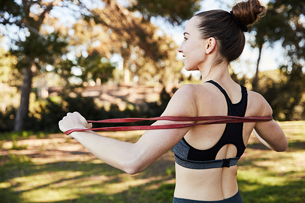 woman using resistance bands outside | resistance bands