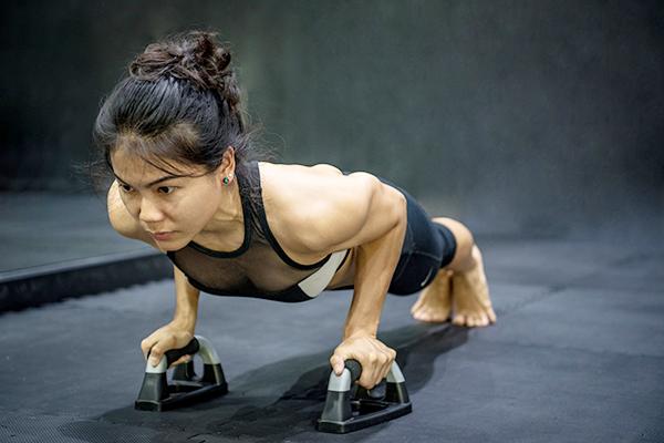 woman using push up bar | sore wrists