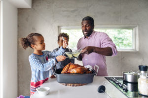 dad making thanksgiving dinner with daughters