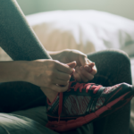 woman tying her shoes for morning run | how to build a habit