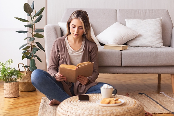 young woman reading a book next to couch | good things that happened in 2020