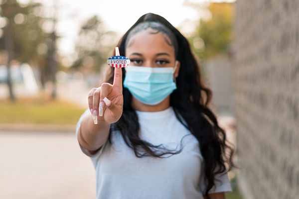 young woman holding up voting sticker | good things that happened in 2020