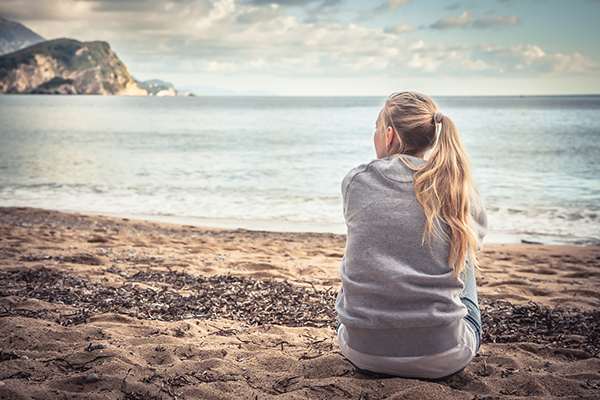 sitting woman looking out into the ocean | meditation challenge