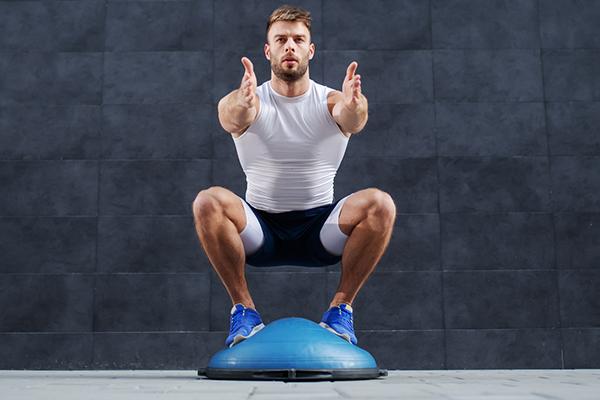 man squatting on bosu ball | proprioception exercises