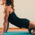 woman foam rolling quad | lying quad stretch
