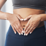 athletic woman holding her stomach | gut health