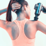 woman using massage gun on shoulder | massage guns