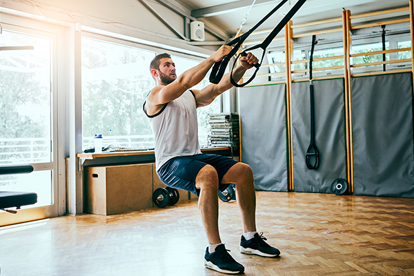 man doing squats on trx trainer | how many squats a day