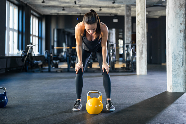 woman resting with kettlebell | how many squats a day