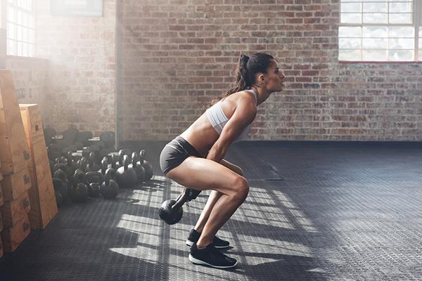 woman doing kettlebell swing in gym | kettlebell swing