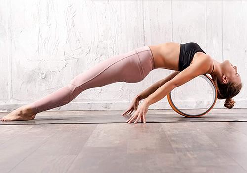 woman doing backbend on yoga wheel | best stretching equipment