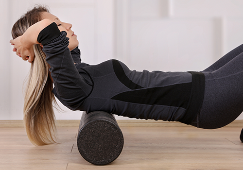 woman foam rolling her back | stretching routine