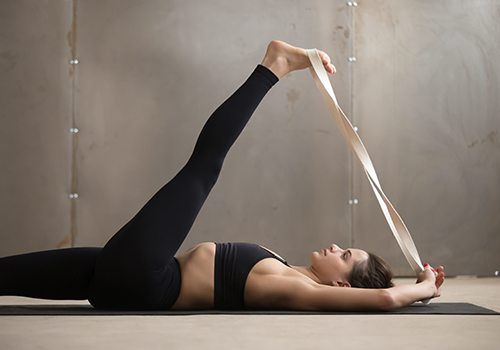 woman stretching with yoga strap   stretching routine