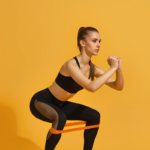 woman doing banded squat | leg exercises with bands