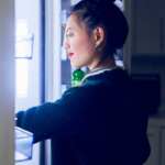 woman looking inside fridge | does eating at night make you gain weight